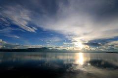 Den härliga solnedgången och aftonhimmel med berget och moln och solnedgången reflekterade i sjön för bakgrund Bygdlandskap U Royaltyfri Bild