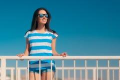 Den härliga sommarmodeflickan i marin gjorde randig skjortan och solglasögon royaltyfria foton