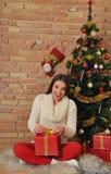 Den härliga spännande unga kvinnan med gåvor near julgranen Arkivbild
