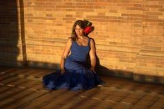 Den härliga spanska kvinnan med blått klär och steg och att sitta för den sista solen Royaltyfri Bild