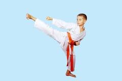 Den härliga sparkfoten utförde vid en pojke med det orange bältet Arkivfoton