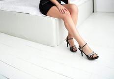 Den härliga spensliga kvinnlign lägger benen på ryggen i häl på en vit bakgrund Royaltyfri Fotografi