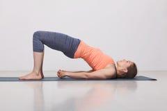 Den härliga sportiga passformyogiflickan öva yoga Arkivbilder