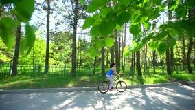 Den härliga sportiga unga kvinnan rider hennes cykel i lyckligt och positivt sätt på varm sommar Flicka på cykeln utanför Sommar stock video