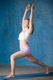 Den härliga sportiga unga kvinnan som gör Virabhadrasana 1, poserar royaltyfri fotografi