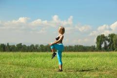 Den härliga sportkvinnan som gör sträcka konditionövning i stad, parkerar på grönt gräs Royaltyfria Bilder
