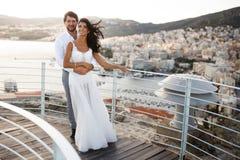 Den härliga ståenden av ett precis gift ungt par, poserar att omfamna bakom av en gammal stads- och havsport, under solnedgång arkivbild