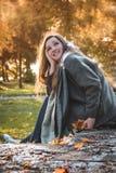 Den härliga ståenden flickan i hösten parkerar Arkivfoton