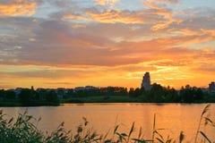 Den härliga staden och guld- solnedgångmoln reflekterade i vatten av po Arkivfoton