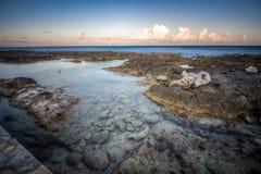 Den härliga steniga stranden på skymning och havet vinkar arkivfoto
