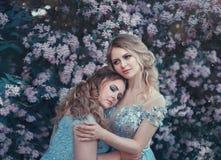 Den härliga stora kvinnan kramar en bräcklig blond flicka Två prinsessor i lyxiga blåa klänningar mot bakgrunden av arkivfoto