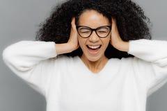 Den härliga stressiga mörka flådde afro- amerikanska kvinnan har huvudvärk, håller båda händer på öron, ignorerar oväsen, har ögo fotografering för bildbyråer