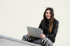 Den härliga studentkvinnan ler genom att använda en bärbar dator och sitta på den gamla väggen i universitetsområdet ursnygg flic royaltyfria bilder
