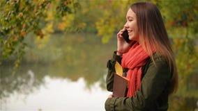 Den härliga studentkvinnlign som talar på mobiltelefonen i höstträdgården nära sjön, härligt skratta för flicka som är offentligt lager videofilmer