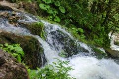 Den härliga tapeten mjölkar strömmen för vattenfallflödesfors Flod Kaukasus för stenigt berg i den skogIsichenko vattenfallet, Gu Royaltyfria Foton