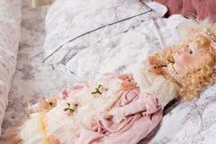 Härlig tappningdocka som ligger på en kudde Arkivfoto