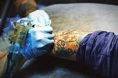 Den härliga tattooisten gör tatueringen arkivbilder