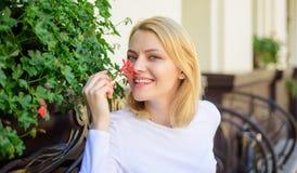 Den härliga terrassen tilldrar klienter Växter som naturlig garnering Flickan sitter kafét sniffar blommaarom Kvinnan sitter kafé arkivbild