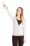 Den härliga tillfälliga kvinnan pekar upp och annonserar. fotografering för bildbyråer