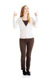 Den härliga tillfälliga kvinnan pekar upp och annonserar. royaltyfri foto