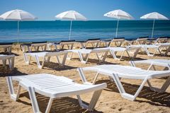 Den härliga tomma stranden med rader av solen bäddar ned under sugrörparaplyer Royaltyfria Foton