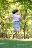 Den härliga tonåriga flickan hoppar utanför på den sunsetBeautiful tonåriga flickan för sommar hoppar utanför på sommarsolnedgång royaltyfri foto
