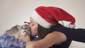 Den härliga tonåriga flickan och hennes katt i Santa Claus caps joyfully att kyssa på vit bakgrund Fotografering för Bildbyråer