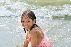 Den härliga tonåriga flickan sitter lyckligt i vågorna som omkring vänder fotografering för bildbyråer