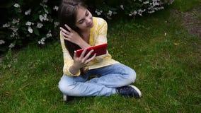 Den härliga tonåringflickan med minnestavladatoren sitter på gräset parkerar in Film av den statiska kameran arkivfilmer