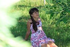 Den härliga tonårs- flickan i rosa färgklänning med långt hår i en grön sommar parkerar Royaltyfri Fotografi