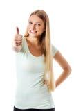 Den härliga tonårs- flickan som ler och gör tummarna-upp, undertecknar Royaltyfri Bild