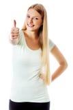 Den härliga tonårs- flickan som ler och gör tummarna-upp, undertecknar Arkivbilder
