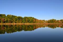 Den härliga trädreflexionen med nedgånghöst färgar på sjön Fotografering för Bildbyråer