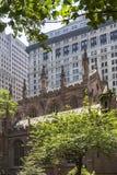 Den härliga Treenighetkyrkan som döljas mellan skyskraporna av Manhattan, New York, Amerikas förenta stater arkivfoton