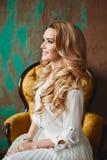 Den härliga trendiga blonda modellflickan med blåa ögon sitter i tappningfåtöljen, inomhus fotografering för bildbyråer