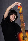 Den härliga trendiga damen som bär en gotisk svart klänning med den höga kragen, poserar med en akustisk gitarr på en grå färg arkivbild