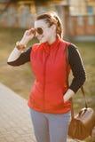 Den härliga trendiga kvinnan trycker på handsolglasögon, stående på solnedgången Iklätt en ljus röd väst, jeans medf8ort arkivfoto