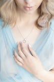 Den härliga trevliga kvinnan i en försiktig luft för blå klänning trycker på försiktigt hjärtan för maskotdräktsmycken Royaltyfria Foton
