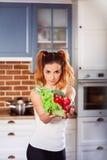 Den härliga tunna flickan står på den moderna kök- och innehavexponeringsglasbunken med ingredienser för grönsaksallad Arkivfoto