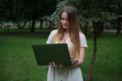 Den härliga ukrainska flickan i den beigea klänningen som in blir, parkerar med bärbara datorn Hon är fri utan kontorsrutin Royaltyfri Bild