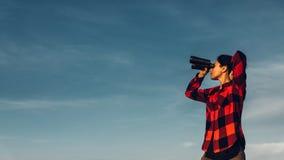 Den härliga ung flickahandelsresanden ser till och med kikare mot en blå himmel med kopieringsutrymme Begreppet av sökandet, moti royaltyfri bild