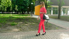 Den härliga unga affärsflickan i röd dräkt och solglasögon går ner gatan på höga häl stock video
