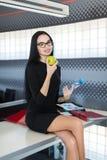 Den härliga unga affärskvinnan i svart klänning och exponeringsglas sitter på tabellen i kontoret och äpplet och flaskan för håll arkivbilder