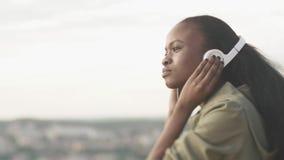 Den härliga unga afrikanska flickan lyssnar till musiken via hörlurar Utomhus- stående för sidonärbild stock video