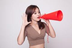 Den härliga unga asiatiska kvinnan meddelar med megafonen Arkivfoto