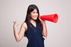 Den härliga unga asiatiska kvinnashowen tummar meddelar upp med megapho Royaltyfri Fotografi