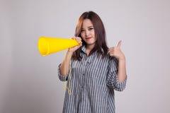 Den härliga unga asiatiska kvinnashowen tummar meddelar upp med megapho Royaltyfri Foto