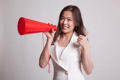 Den härliga unga asiatiska kvinnashowen tummar meddelar upp med megapho Arkivbilder