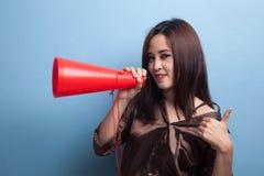 Den härliga unga asiatiska kvinnashowen tummar meddelar upp med megapho Royaltyfria Bilder
