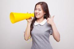 Den härliga unga asiatiska kvinnashowen tummar meddelar upp med megapho Royaltyfri Bild